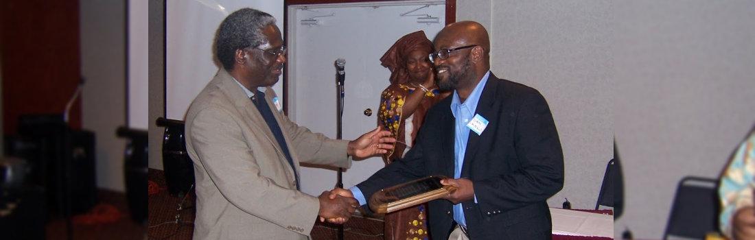 man receiving award and giving handshake